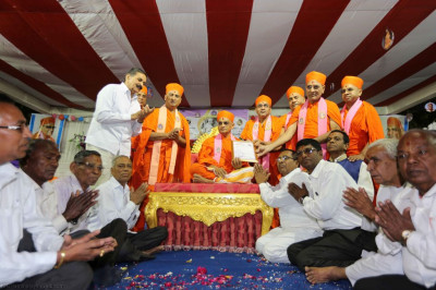 Sants and disciples present the honour from a local dignatory to Acharya Swamishree