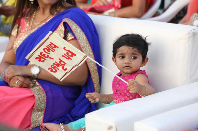 A very young disciple waves a Sadbhav Amrut Parva flag