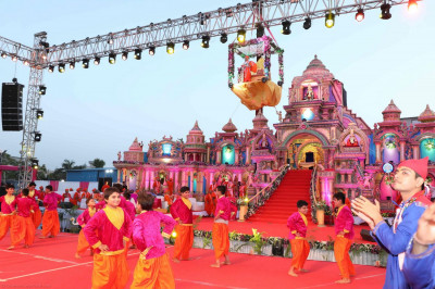 Disciples perform a welcome dance as Acharya Swamishree descends down onto the grand stage