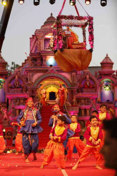 Young disciples dance joyously to welcome Acharya Swamishree onto the grand stage