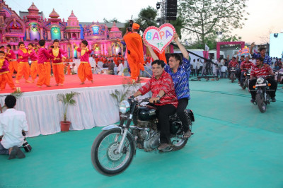 Disciples circle the stage on motorbikes while holding up signs to celebrate Acharya Swamishree's Sadbhav Amrut Parva