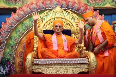 Acharya Swamishree presides on the grand stage and bestows His divine darshan upon the entire congregation gathered for the celebrations