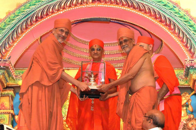Shree Prem Swami and Shree Tyagvallabh Swami from Sokhda Shree Swaminarayan Mandir present Acharya Swamishree with a kumbh memento