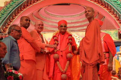 Sri Swami Adhyatmanandji and other Sants from Sivananda Ashram honor Acharya Swamishree with a grand garland