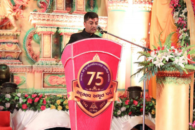 Dr. Maheshbhai Varsani gives a speech on the ongoing charitable humanitarian efforts undertaken by Maninagar Shree Swaminarayan Gadi Sansthan under the guidance of Acharya Swamishree