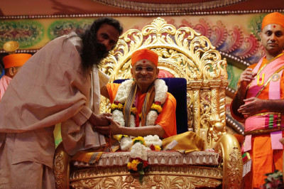 Shri Akhileshji Maharaj greets Acharya Swamishree and honors Him with a saal and garland