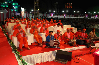 Sants and disciples sing and clap along with the dhoon following Acharya Swamishree's manglacharan at the start of His divine blessings for the evening