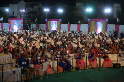 The audience waves their Sadbhav Amrut Parva flags in celebration