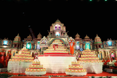 Standing between the grand celebration cakes, Acharya Swamishree bestows His divine darshan and waves to the entire audience