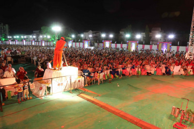 The entire audience performs aarti to Acharya Swamishree with individual tealights