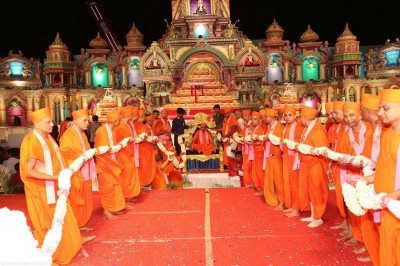 Sants and disciples adorn Acharya Swamishree in a 75-foot long fresh flower garland