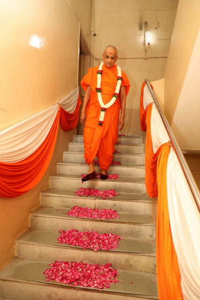 Acharya Swamishree descends down the steps from His living quarters lined with fresh flower petals