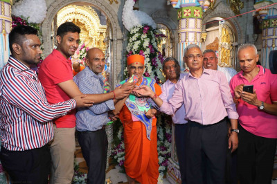 Sponsor disciples offer cake to Acharya Swamishree on His 75th manifestation day