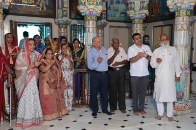 Disciples perform aarti to Acharya Swamishree on His 75th manifestation day
