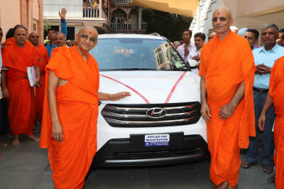 Divine darshan of Acharya Swamishree with a new car donated on His 75th manifestation day