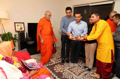 Disciples welcome His Divine Holiness Acharya Swamishree, sants and disciples into their home and offer aarti