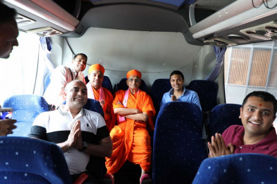 Divine darshan of Acharya Swamishree seated on the back seat of one of the coaches with disciples