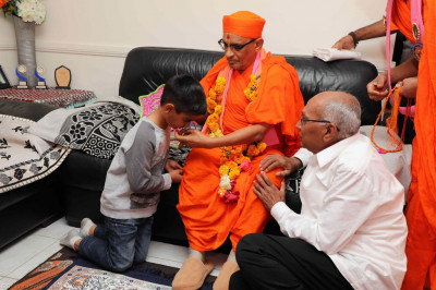 His Divine Holiness Acharya Swamishree presents a kanthi to a young disciple