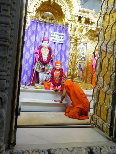 His Divine Holiness Acharya Swamishree bows down to the divine lotus feet of Sadguru Shree Gopalanand Swamibapa
