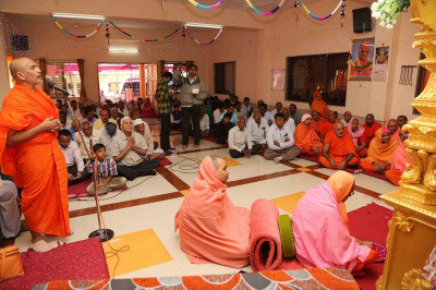 His Divine Holiness Acharya Swamishree showers rose petals at the lotus feet of the Lord