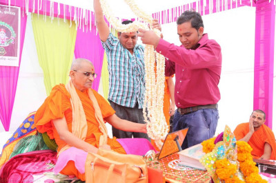 Disciples present a garland made from popcorn to His Divine Holiness Acharya Swamishree