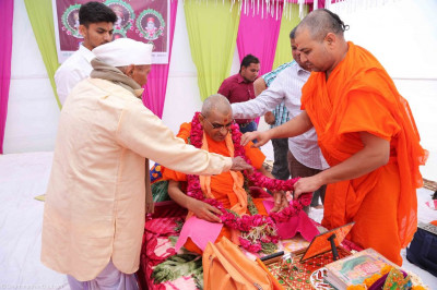 Disciples present a garland of bright red fresh roses to Acharya Swamishree