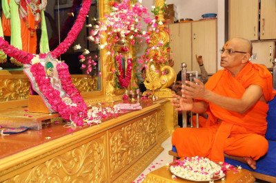 His Divine Holiness Acharya Swamishree showers flower petals at the divine lotus feet of the Lord