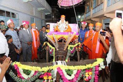 Divine darshan of Acharya Swamishree seated upon the traditional village chariot decorated with fresh bright fragrant flowers