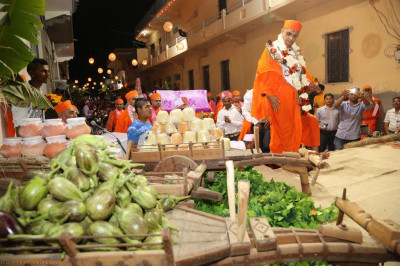 Divine darshan of Acharya Swamishree surrounded by various fresh fruit and vegetables