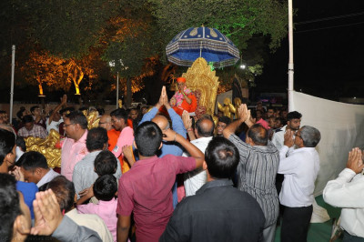 His Divine Holiness Acharya Swamishree showers His divine blessings on all seated on the goldern chariot