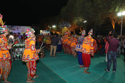 Young disicples dressed in colourful Indian traditional village costumes perform devotional dances with dandia sticks as His Divine Holiness Acharya Swamishree arrives