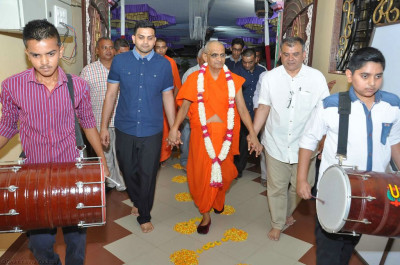 Disciples escort His Divine Holiness Acharya Swamishree to the mandir as disciples play dhol