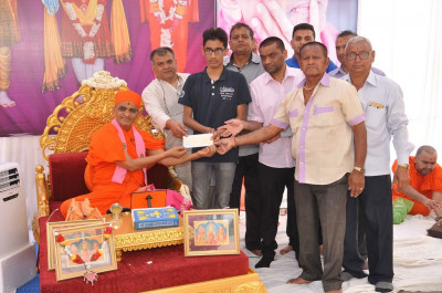 His Divine Holiness Acharya Swamishree presents cheques to various local charitable organisations