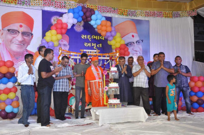 His Divine Holiness Acharya Swamishree lights the candle on the three tier cake