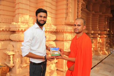 Sant presents prasad to the honoured guest