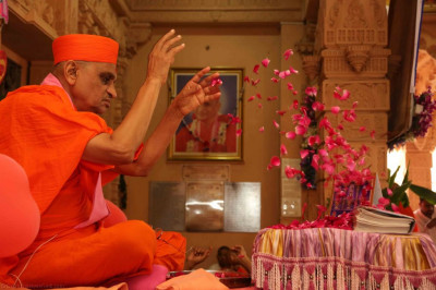 His Divine Holiness Acharya Swamishree showers flower petals at the lotus feet of the Lord