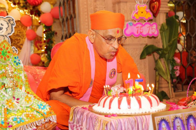 His Divine Holiness Acharya Swamishree blows out the candles on the celebration cake