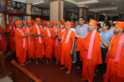 Acharya Swamishree Maharaj, sants, and disciples perform aarti