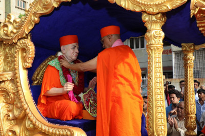 Acharya Swamishree maharaj puts a garland on Jeevanpran Swamibapa who is seated on a chariot