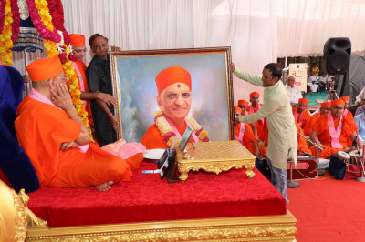 A portrait of Acharya Swamishree Maharaj being presented