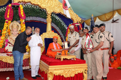 Members of Civil Defence Gujarat State present a memento to Acharya Swamishree Maharaj