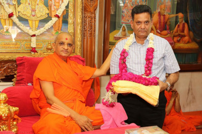 His Divine Holiness Acharya Swamishree presents prasad shawls and a garland of flowers