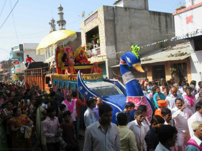 The procession proceeds through the main village street