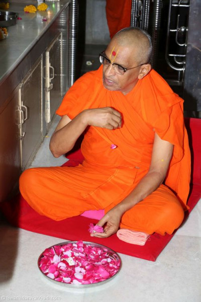 His Divine Holiness Acharya Swamishree showers fresh fragrant flowers at the lotus feet of the Lord