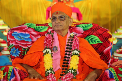 Divine darshan of Acharya Swamishree seated in front of 75 cakes arranged in a heart