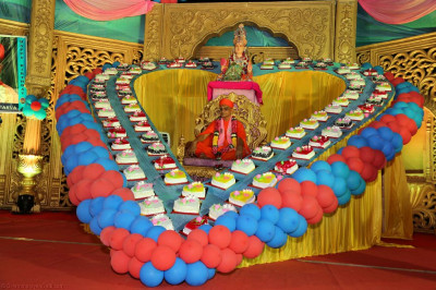 Divine darshan of Acharya Swamishree seated within the heart surrounded by 75 cakes