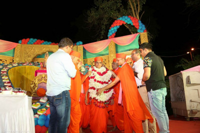 Sants and disciples present a shawl made of flowers to His Divine Holiness Acharya Swamishree
