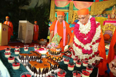 His Divine Holiness Acharya Swamishree cuts the cake and offers a piece to Shree Harikrishna Maharaj
