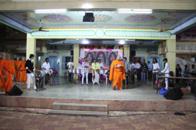 Sants and disciples perform devotional songs as all play raas