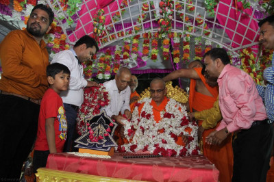 Disicples offer large garlands of fresh flowers to His Divine Holiness Acharya Swamishree